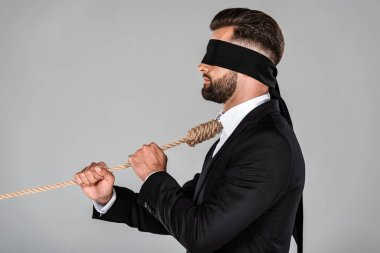 side view of blindfolded businessman in black suit with noose on neck holding rope isolated on grey