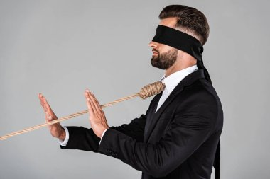 side view of blindfolded businessman in black suit with noose on neck showing stop gesture isolated on grey