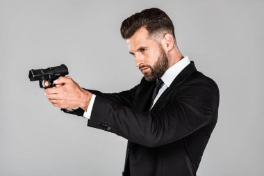 Handsome agent in black suit aiming gun isolated on grey stock vector
