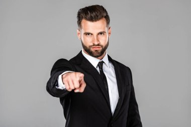successful businessman in black suit pointing with finger at camera isolated on grey