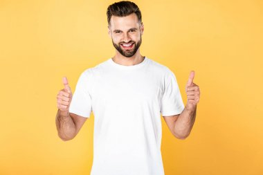 Happy handsome man in white t-shirt showing thumbs up isolated on yellow stock vector
