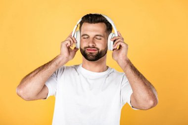 happy handsome man in white t-shirt listening music in headphones with closed eyes isolated on yellow