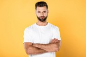 Photo handsome man in white t-shirt with crossed arms isolated on yellow