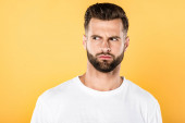 Fotografie worried handsome man in white t-shirt looking away isolated on yellow
