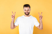 šťastný pohledný muž v bílém tričku, který se dívá na kameru a ukazuje mírové signály izolované na žluté