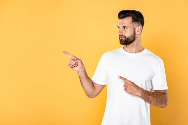 Handsome man in white t-shirt pointing with fingers aside isolated on yellow stock vector