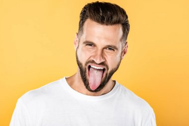 handsome funny man showing tongue isolated on yellow