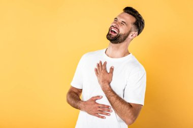 happy handsome man in white t-shirt laughing isolated on yellow