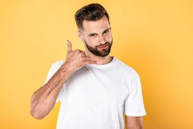 smiling handsome man in white t-shirt showing call me gesture isolated on yellow