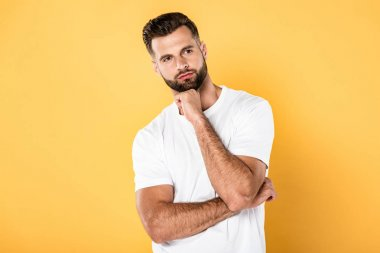 Pensive man in white t-shirt looking away isolated on yellow stock vector