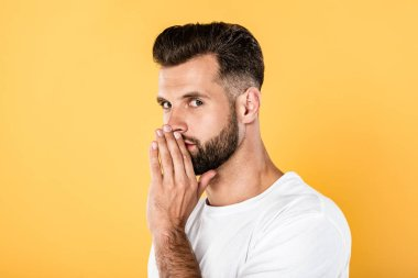 handsome man in white t-shirt whispering isolated on yellow