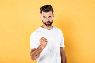 angry handsome man in white t-shirt showing fist isolated on yellow