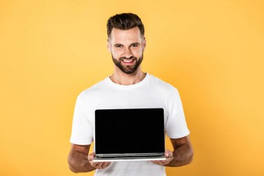 Happy handsome man in white t-shirt showing laptop with blank screen isolated on yellow stock vector