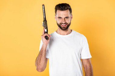 Smiling handsome man in white t-shirt holding revolver isolated on yellow stock vector