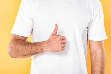 Cropped view of man in white t-shirt showing thumb up isolated on yellow stock vector