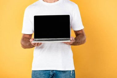 Partial view of man in white t-shirt showing laptop with blank screen isolated on yellow stock vector