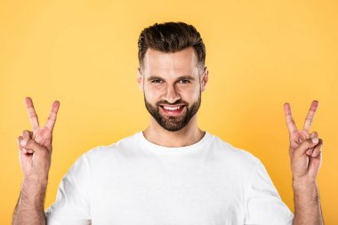 Smiling handsome man in white t-shirt looking at camera and showing peace signs isolated on yellow stock vector