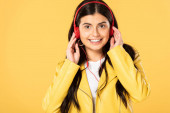 Photo smiling girl listening music with headphones, isolated on yellow
