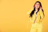 lächelndes attraktives Mädchen, das Musik mit Kopfhörern hört, isoliert auf gelb