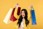 izgatott lány bevásárló táskák, izolált sárga