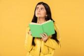 gyönyörű diák gondolkodás tartva ceruza és könyv, elszigetelt sárga