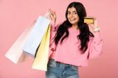 attraktives Mädchen mit Kreditkarte und Einkaufstaschen, isoliert auf rosa