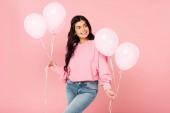 krásná usměvavá dívka držící růžové balónky, izolované na růžovém