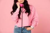 oříznutý pohled na ženu mluvící na retro telefonu izolovaná na růžovém