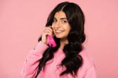 Fotografie fröhliches Mädchen spricht am Retro-Telefon isoliert auf rosa