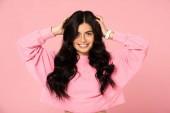 Fotografie usmívající se brunetka v příležitostným oblečení, které představuje izolované na růžovém