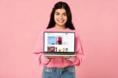 Kijev, Ukrajna-július 30, 2019: mosolygós lány kezében laptop az eBay honlapján a képernyőn, izolált rózsaszín