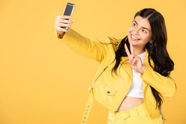 beautiful girl showing victory sign and taking selfie on smartphone, isolated on yellow