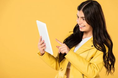 beautiful woman using digital tablet, isolated on yellow