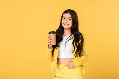 beautiful brunette girl with coffee to go isolated on yellow