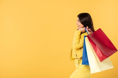Happy girl with shopping bags, isolated on yellow stock vector