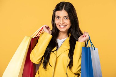 cheerful beautiful woman holding shopping bags, isolated on yellow