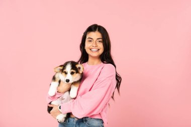 smiling woman holding Welsh Corgi puppy, isolated on pink