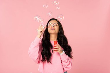 attractive girl blowing soap bubbles isolated on pink