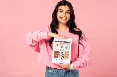 KYIV, UKRAINE - JULY 30, 2019: smiling girl holding digital tablet with pinterest app on screen, isolated on pink stock vector