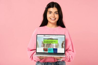 KYIV, UKRAINE - JULY 30, 2019: smiling girl holding laptop with BBC website on screen, isolated on pink stock vector