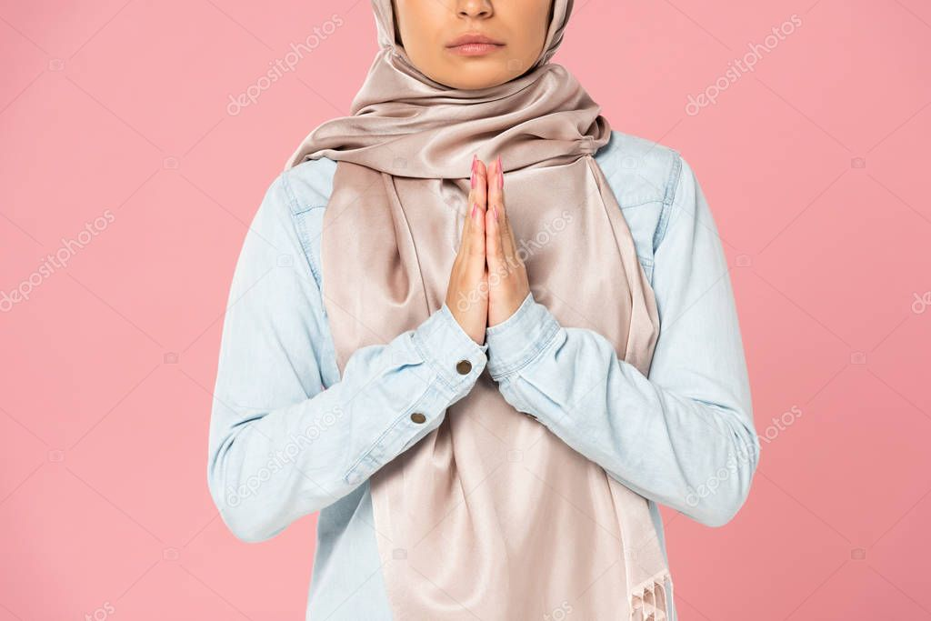 Cropped view of muslim girl in hijab praying, isolated on pink stock vector