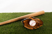 Photo baseball bat, glove and ball on green grass isolated on white, sports betting concept