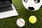 soccer, baseball and tennis balls near laptop on green grass, sports betting concept