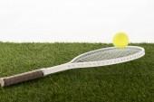 teniszütő és labda zöld füvön elszigetelt fehér, sportfogadás koncepció