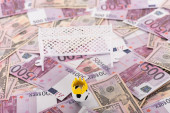 toy soccer ball with paper crown near miniature football gates on euro and dollar banknotes, sports betting concept
