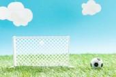 hračky fotbalové brány a míč na zelené trávě na modrém pozadí s mraky, sportovní sázení koncept