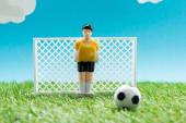 Spielzeug-Torwart in der Nähe von Miniatur-Fußballtoren und Ball auf blauem Hintergrund mit Wolken, Sportwetten-Konzept