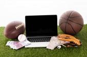 laptop sportlabdák közelében, baseball kesztyű, euro és dollár bankjegyek zöld füvön elszigetelt fehér, sportfogadás koncepció