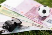 selektivní zaměření píšťalky, fotbalových míčků a eurobankovek na zelenou trávu, koncept sportovního sázení