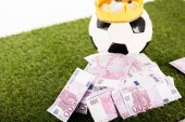 Fotografia euro banknotes near soccer ball with paper crown on green grass isolated on white, sports betting concept